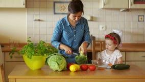 Den unga brunetten klipper grönsaker i köket Hon tog broccoli och morötter Hennes lilla dotter hjälper hennes moder lager videofilmer