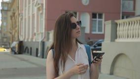Den unga brunetten med telefonen är på stadsgatan i sommareftermiddag stock video