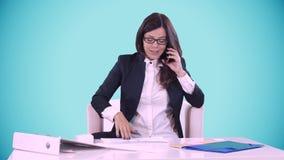 Den unga brunetten på en blå bakgrund sitter bak ett skrivbord i regeringsställning och tala på telefonen På tabellen är dokument lager videofilmer