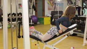 Den unga brunetten utarbetar med handvikter i idrottshall stock video