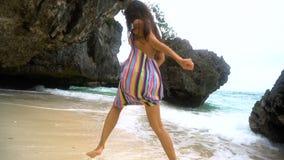 Den unga brunettflickan i en ljus klänning kör längs den vita stranden och att le på kameran som framkallar hår lager videofilmer