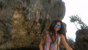 Den unga brunettflickan i en ljus klänning kör längs den vita stranden och att le på kameran som framkallar hår stock video
