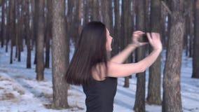 Den unga brunettflickan i en svart klänning gör selfie med hennes smartphone i en vinterskog som ler att vända omkring arkivfilmer