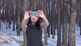 Den unga brunettflickan i en svart klänning gör selfie i en vinterskog stock video
