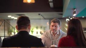 Den unga brunettflickan introducerar hennes pojkvän till hennes fader i ett kafé stock video