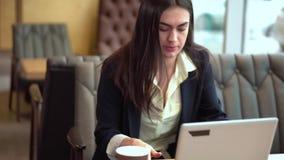 Den unga brunettflickan med en bärbar dator och ett kaffe i händer skynda sig för att sitta ner på en tabell för att kontrollera  lager videofilmer