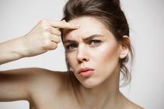 Den unga brunettflickan misshog av hennes hud för problemakneframsidan över vit bakgrund Vård- cosmetology och skincare arkivbilder