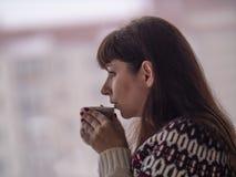 Den unga brunettkvinnan dricker kaffe och ser ut fönstret hänsynsfullt arkivfoto
