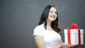 Den unga brunettkvinnan ger en gåva på grå bakgrund white för band för askgåva röd