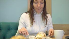 Den unga brunettkvinnan i kafé äter efterrätten stock video