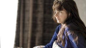 Den unga brunettkvinnan ler, medan sitta i morgonen i hennes säng arkivbild