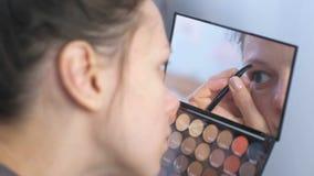 Den unga brunettkvinnan plockar hennes ögonbryn med pincett framme av spegeln hemma lager videofilmer