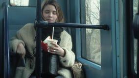 Den unga brunettkvinnan rider p? kollektivtrafik, bruk telefonen med h?rlurar arkivfilmer