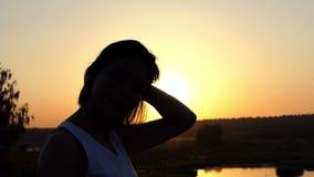 Den unga brunettkvinnan sätter hennes hår i beställning på en sjöbank på solnedgången i ultrarapid stock video