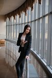 Den unga brunettkvinnan ser till och med fönstret på nivåerna och väntar till avvikelsen i flygplats arkivfoton