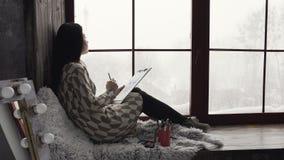 Den unga brunettkvinnan sitter på en fönsterbräda nära fönster och drar i hennes sketchbook Inspirerad kvinnlig konstnär in arkivfilmer