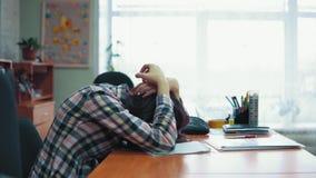 Den unga brunettkvinnan sitter på en tabell i ett tillstånd av nöd med en huvudvärk