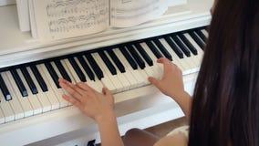 Den unga brunettkvinnan spelar pianot i ljust rum, handen - rymt skott stock video