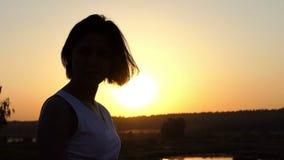 Den unga brunettkvinnan ställer in hennes hår upp på en sjöbank på solnedgången i ultrarapid lager videofilmer