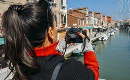 Den unga brunettkvinnan tar en bild av en färgrik kanal i Murano med en DSLR-kamera arkivfoto