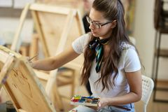 Den unga brunhåriga flickan i exponeringsglas iklädd vit t-skjorta och jeans med en halsduk runt om hennes hals målar en bild  royaltyfria bilder