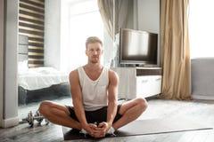 Den unga brunn-byggda mannen går in för sportar i lägenhet Lugna och fridsamma grabbhållhänder på fot och elasticitetsben Grön tr arkivfoto