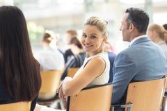 Den unga Caucasian affärskvinnan satt i konferensrum som ler till kameran royaltyfria foton