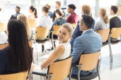 Den unga Caucasian affärskvinnan satt i konferensrum som ler till kameran royaltyfri foto