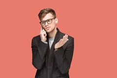 Den unga caucasian affärsmannen på röd bakgrund som talar på mobiltelefonen Arkivfoton