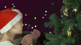 Den unga caucasian flickadottern med fadern i röd jultomtenhatt dekorerar det gröna julträdet med den guld- sfärbollen lager videofilmer