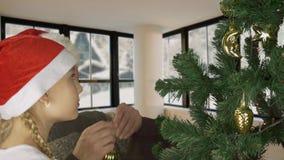 Den unga caucasian flickadottern med fadern i röd jultomtenhatt dekorerar den gröna guld- bollen för julträdet Glade Prepairing lager videofilmer