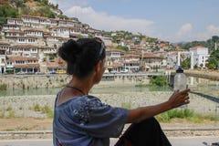 Den unga Caucasian flickahandelsresanden sitter med hennes baksida till kameran och blickar på den albanska staden av Berat royaltyfri fotografi