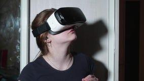 Den unga caucasian flickan i VR-exponeringsglas ser omkring förskräckt och trycker på dörren av garderoben arkivfilmer