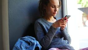 Den unga caucasian flickan tycker om en mobil smartphone på ett kaféfönster stock video
