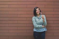 Den unga caucasian kvinnan i ett grått läderomslag smakar iscrea Arkivfoto