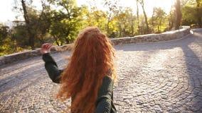 Den unga caucasian kvinnan i den svarta stack tröjan som kör joyfully i en färgrik höst, parkerar på trottoar Rött lockigt haired lager videofilmer