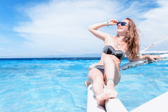 Den unga caucasian kvinnan med solglasögon sitter på fartyget i det tropiska turkoshavet och får solbränna på den soliga dagen Royaltyfri Bild