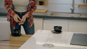 Den unga caucasian kvinnan sätter kaffekoppen på skrivbordet i hem- kök arkivfilmer