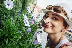 Den unga caucasian kvinnan sniffar härliga blommor Arkivbild