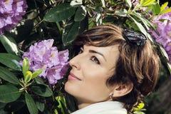 Den unga caucasian kvinnan sniffar purpurfärgade blommor i parkera Royaltyfri Bild