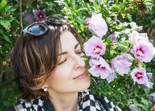 Den unga caucasian kvinnan sniffar rosa blommor i parkera Arkivbild