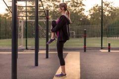 Den unga caucasian kvinnan värmer upp på parkerar sportjordning Flickan i sportar poserar upp benet på räkningen, i svart sportsw fotografering för bildbyråer