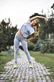 Den unga caucasian kvinnliga joggeren gör uppvärmning, innan det joggar royaltyfri bild