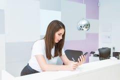 Den unga caucasian kvinnliga receptionisten som ser på den smarta telefonen och, gör anmärkningar Administratör chef i kontoret,  arkivfoton