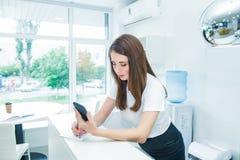 Den unga caucasian kvinnliga receptionisten som ser på den smarta telefonen och, gör anmärkningar Administratör chef i kontoret,  royaltyfria foton