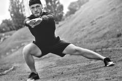 Den unga caucasian manliga joggeren med konditionbogseraren som fästas för att beväpna, gör uppvärmning, innan det joggar royaltyfria bilder