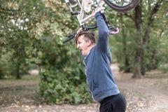 Den unga caucasian mannen kraschar hans cykel ner med sinnesrörelser royaltyfri bild