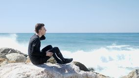 Den unga caucasian mannen som sitter p?, vaggar med fingrar i hans h?r Starka havv?gor som sl?r den steniga stranden med att plas arkivfilmer