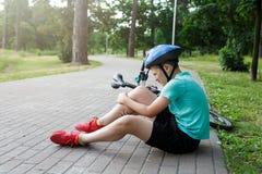 Den unga caucasian pojken i hjälm och grön t-skjorta fick olycka och sitter på jordningen, når han har fallit från cykeln och kän royaltyfria foton