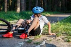 Den unga caucasian pojken i hjälm och den vita t-skjortan fick olycka och sitter på jordningen, når han har fallit från cykeln oc royaltyfri bild